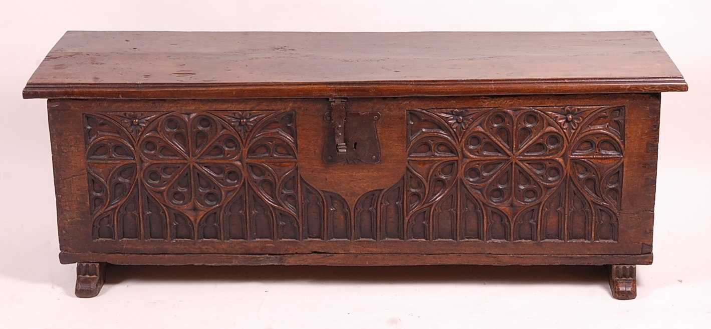 An antique joined and heavy planked oak blanket chest, having Gothic Revival relief carved front