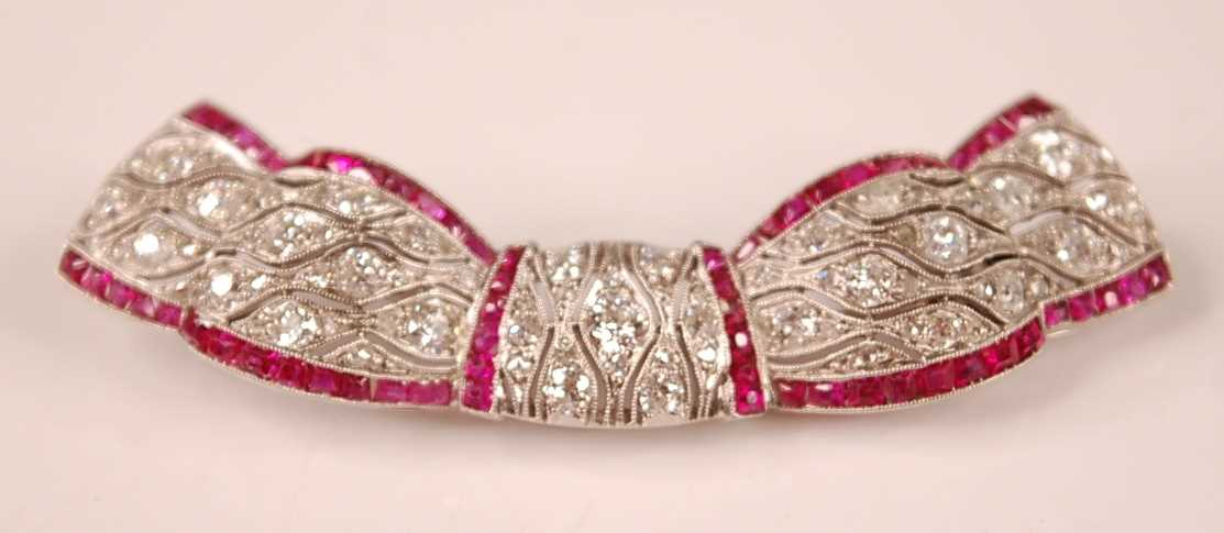 An Art Deco style white metal, ruby and diamond swag shaped bar brooch, comprising 81 Old European