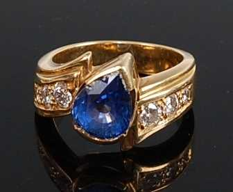 An 18ct yellow gold, tanzanite and diamond crossover style ring, featuring a pear cut tanzanite in a