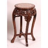 A circa 1900 Chinese 'rosewood' and variegated marble inset low jardiniere stand, of circular