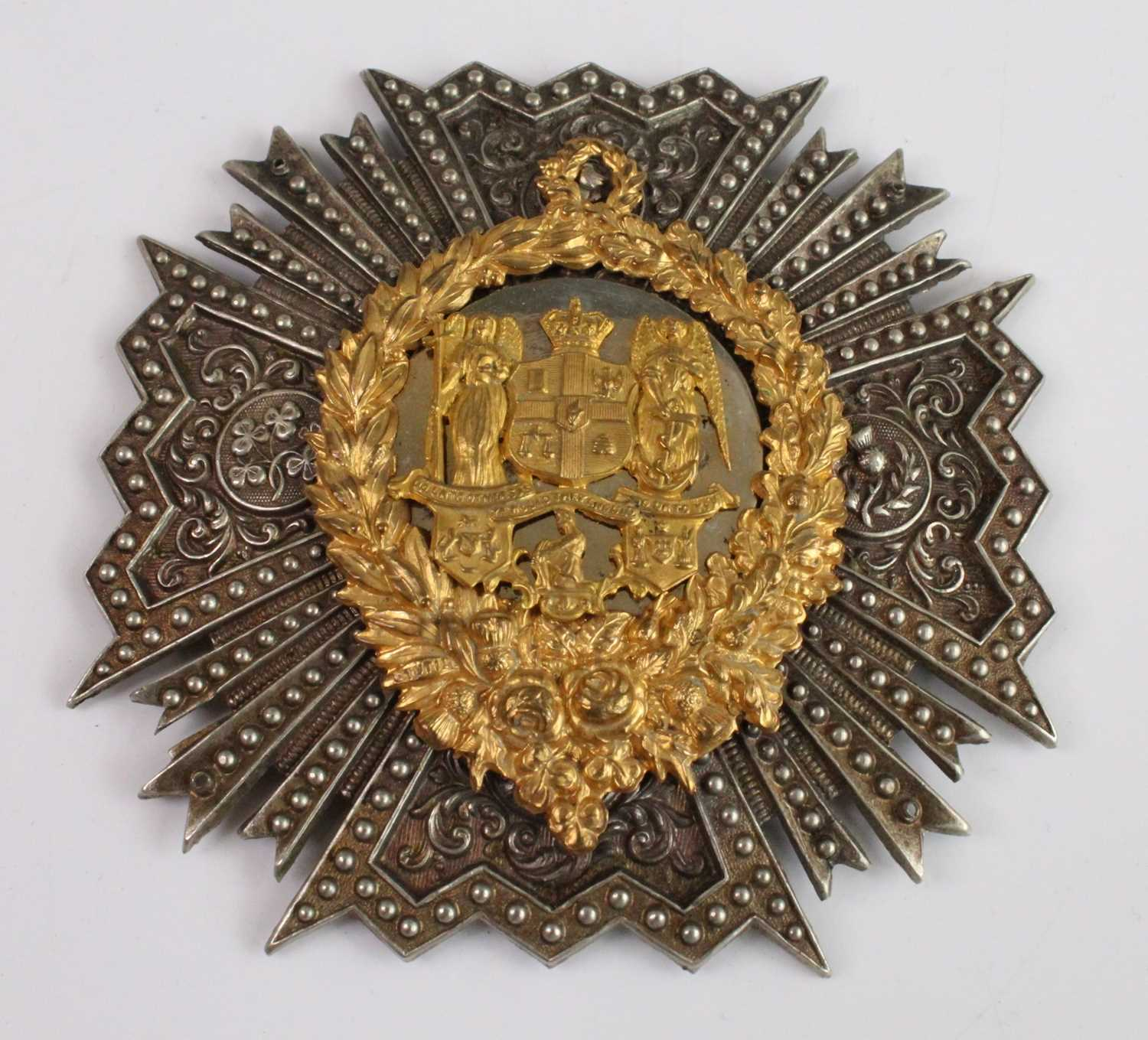 """A helmet plate the gilt centre with a crowned shield flanked by winged figures with """"The Golden"""