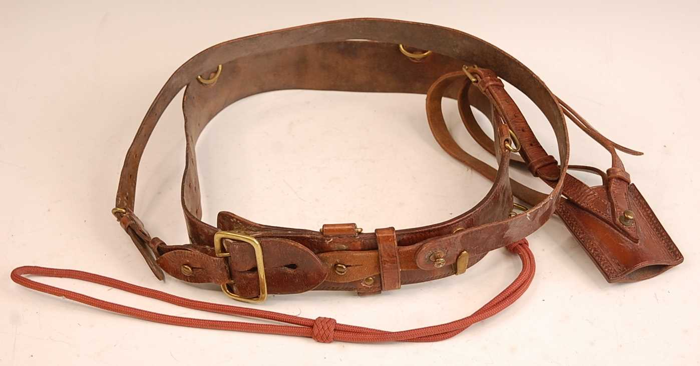 A brown leather and brass mounted Sam Browne belt with cross strap and sword frog.