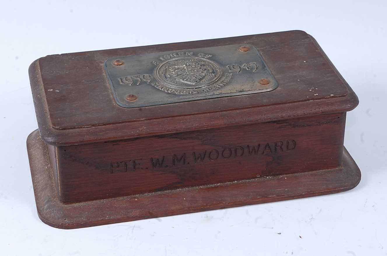 An oak commemorative table cigarette box, the hinged lid with applied plaque with Stamford crest