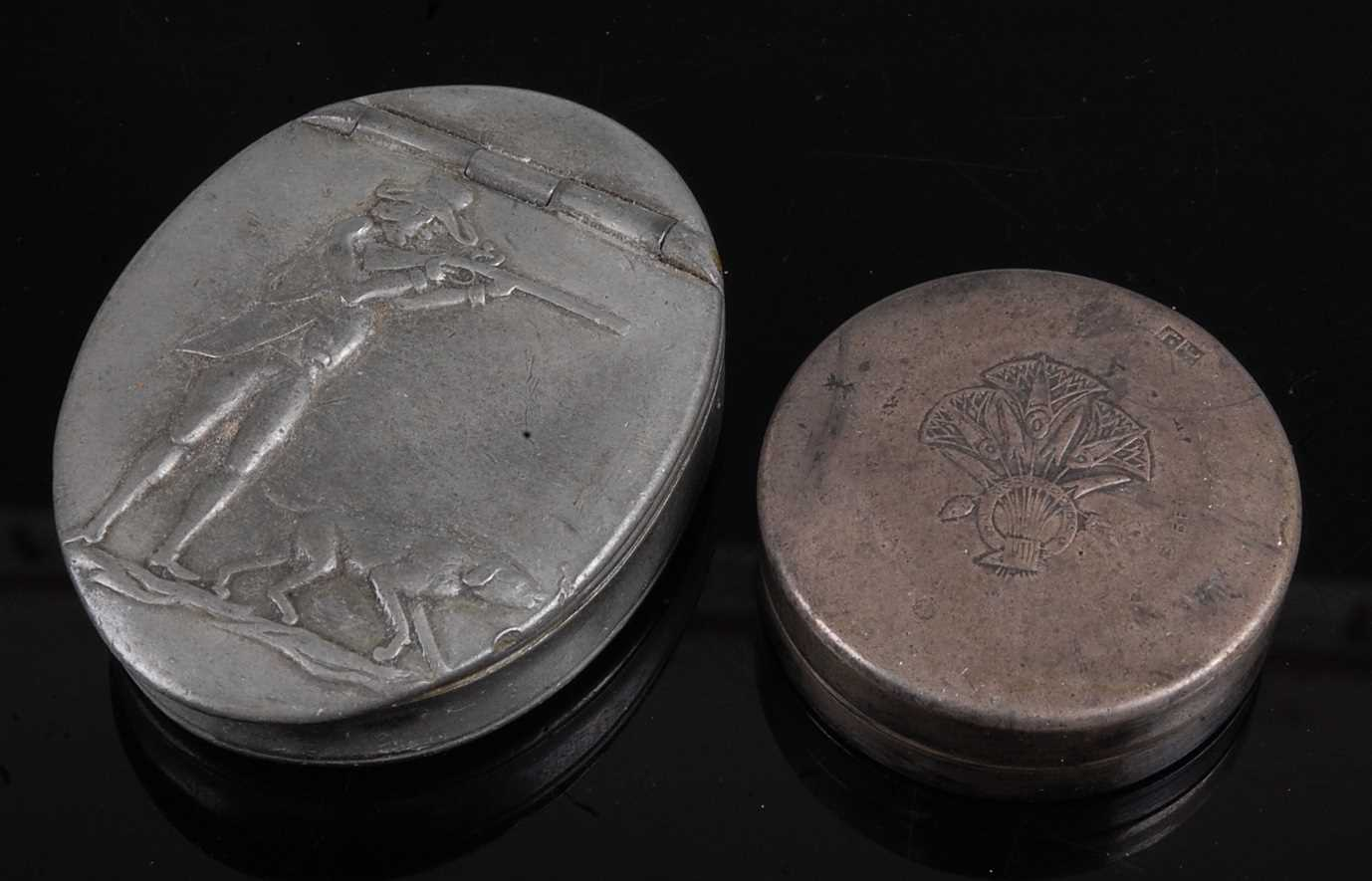 A pewter snuff box of oval form, the hinged cover relief decorated with a huntsman and hound,