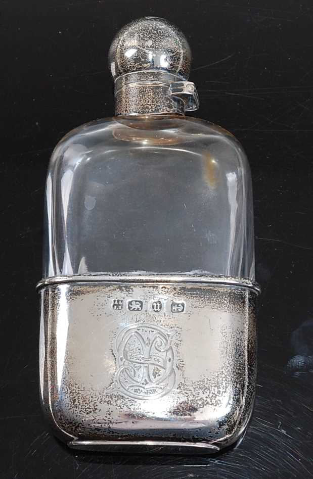 A late Victorian pocket hip flask, having a glass body with silver bayonet cap and removable cup
