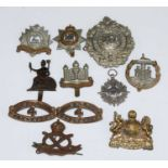 A collection of cap badges and insignia to include Mancester Regiment, South Staffordshire,
