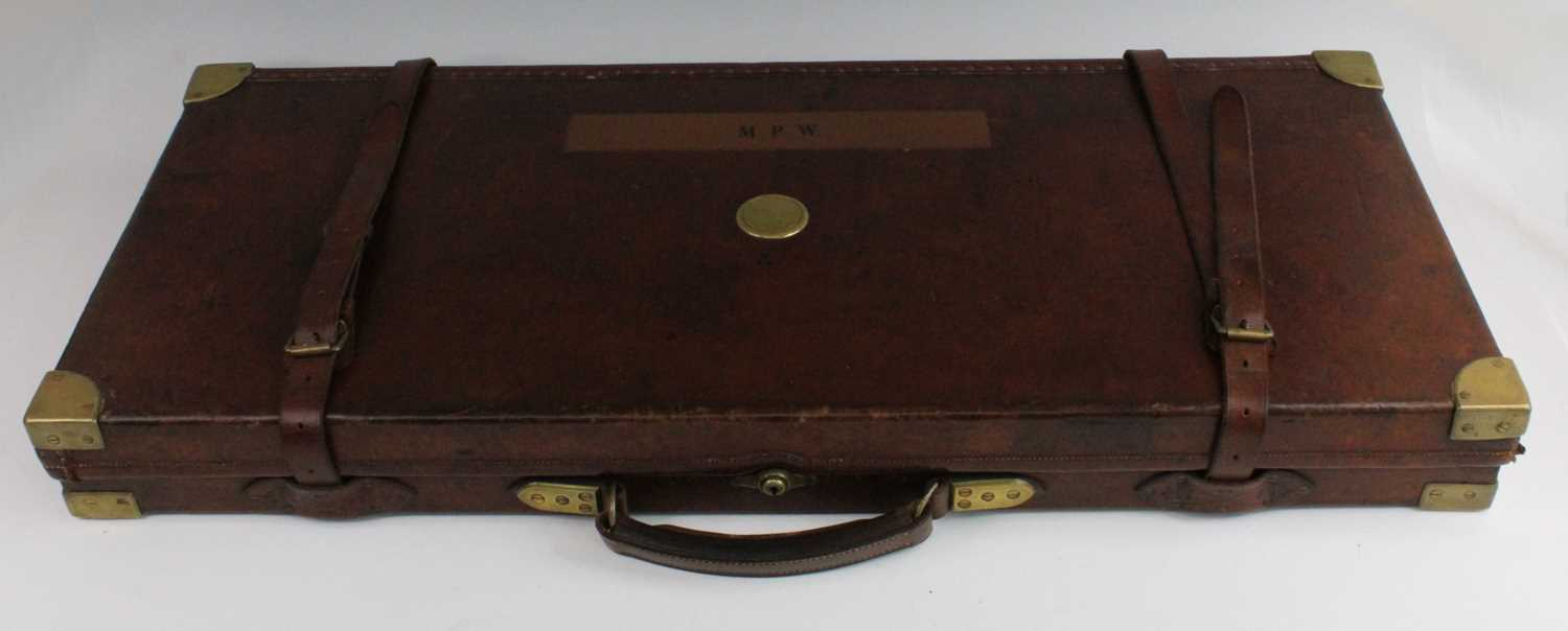 A late Victorian leather clad and brass bound oak shotgun case, having a felt lined interior for two