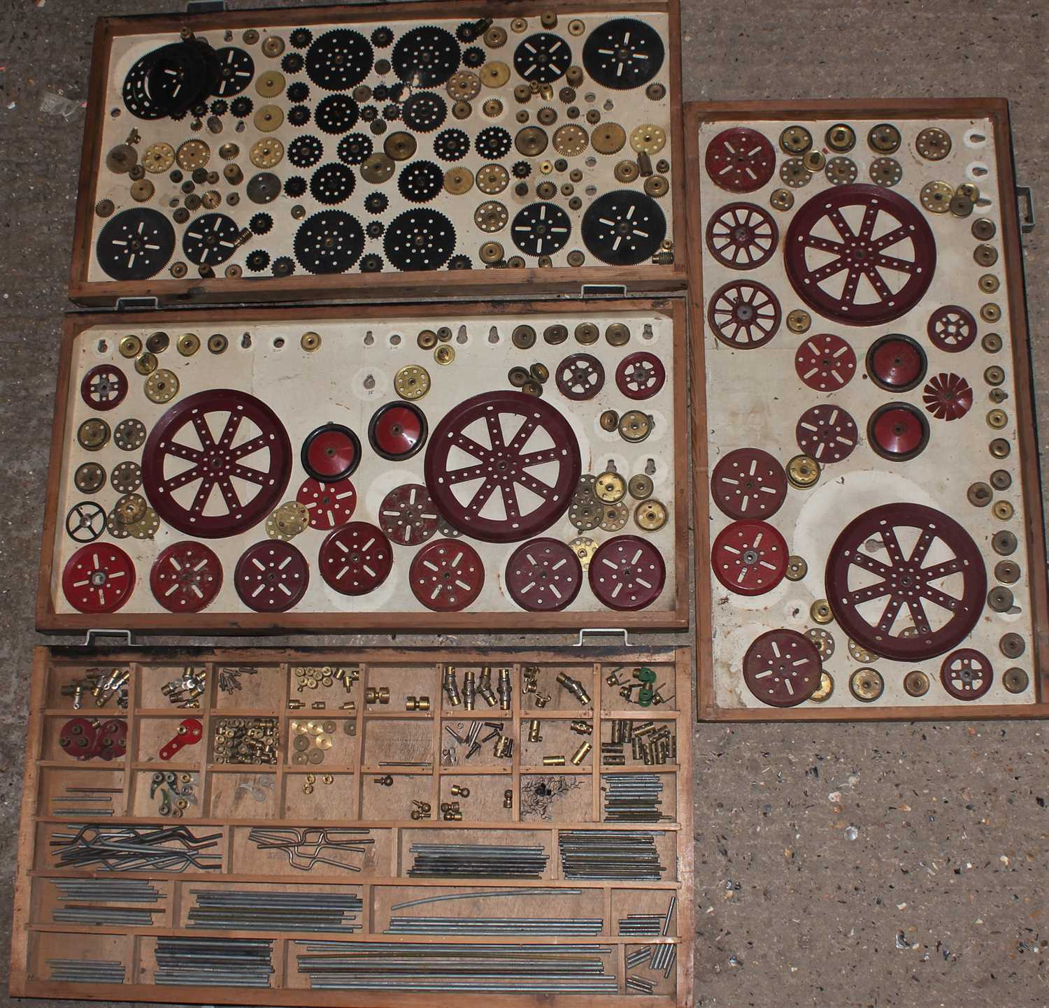 Four trays containing a quantity of mixed red and brass, and black 1950s and later Meccano, mixed