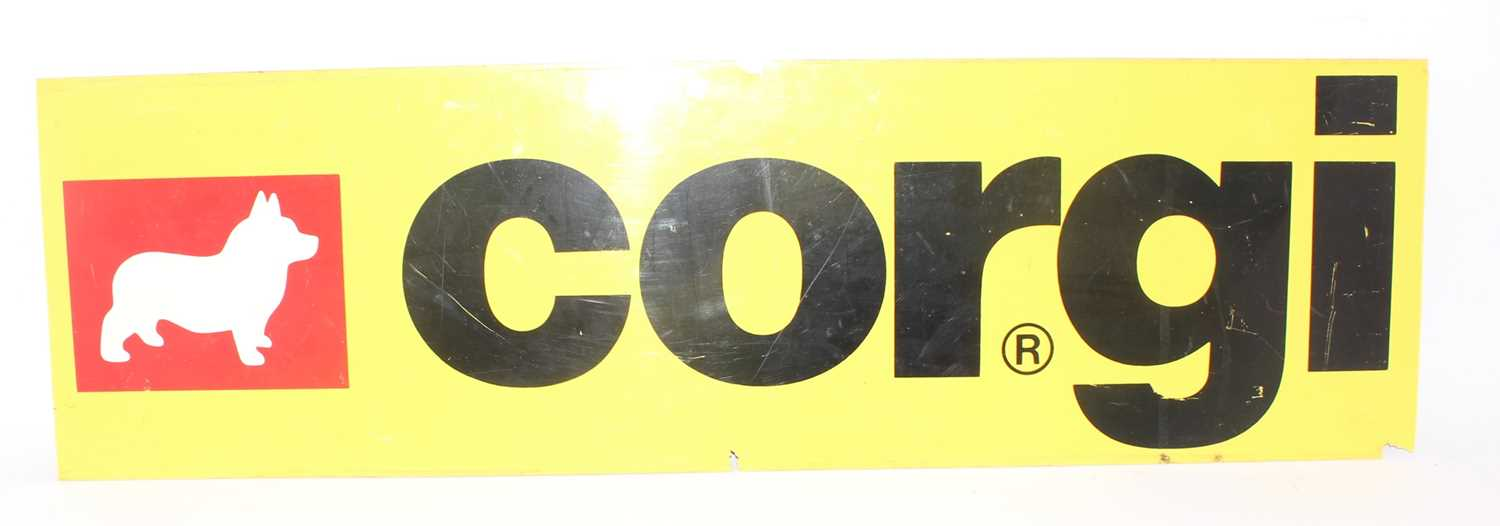 A Corgi Toys 1970s plexiglass advertising shop display sign, yellow ground with black lettering, and