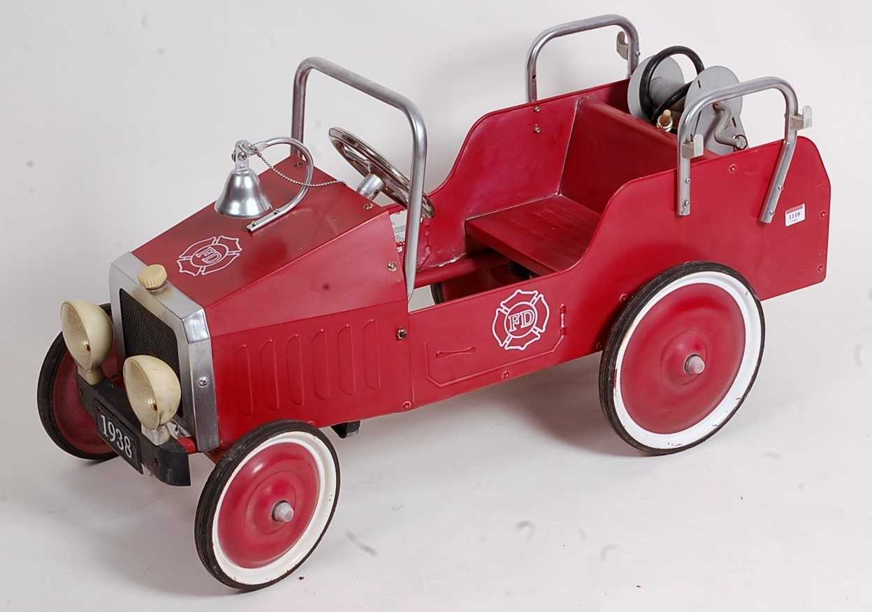 Modern release child's fire department pedal car finished in red and silver with red and white hubs.