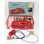 A Schuco No. 5311 Elektro Ingenico tinplate and battery-operated saloon, comprising of red body with
