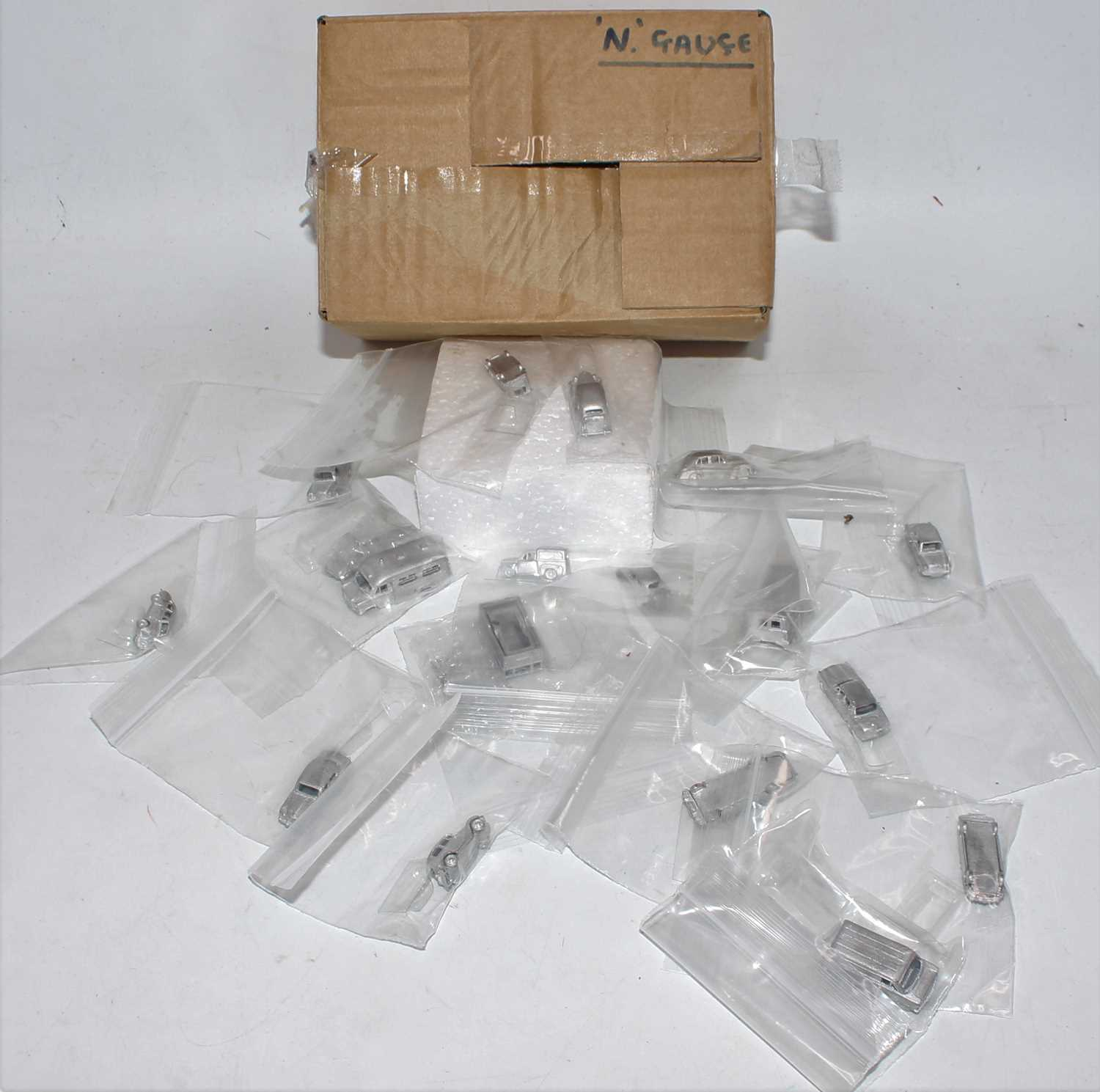 A small quantity of various white metal N gauge vehicles, to include delivery vans, caravans,