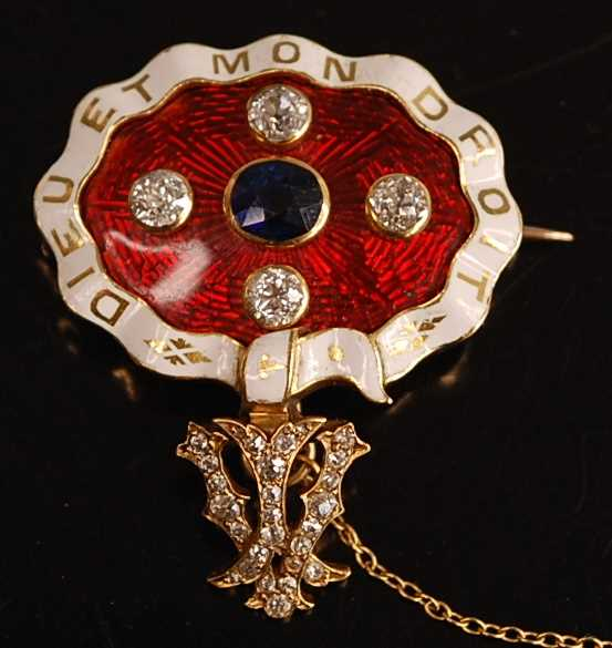 A yellow metal, sapphire and diamond enamel brooch, comprising an oval panel in red guilloche enamel