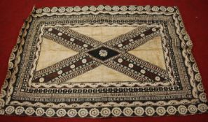 A Batik style wall hanging, having a central cross design in shades on brown and black within
