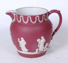 A Wedgwood crimson Jasperware jug, circa 1870, relief decorated with classical figures and swags,
