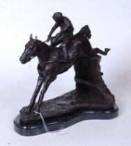 A bronzed figure of a racehorse and jockey jumping a hurdle, on naturalistic base and marble plinth,