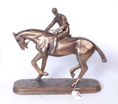 A reproduction bronzed resin figure of a racehorse and jockey, on naturalistic oval plinth, h.32cm