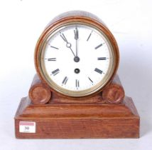 A late Victorian oak cased drumhead mantel clock, having an enamelled dial with Roman numerals and