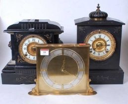 A late Victorian black slate mantel clock of architectural form having an enamelled chapter ring