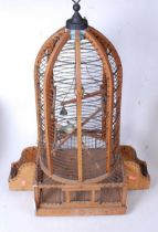 A large softwood and wirework birdcage, of domed form, containing two model birds, h.75cm