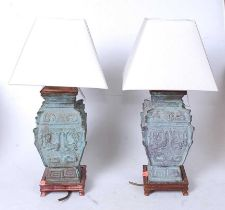 A pair of Chinese bronze table lamps, of square section, having incised Greek Key type decoration