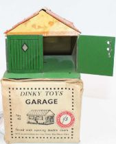 A Dinky Toys Pre-War No.45 tinplate Garage comprising of green, cream, and orange body with green