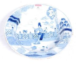 An 18th century tin-glazed dish, decorated in the Chinese taste with a figure before a fence, dia.
