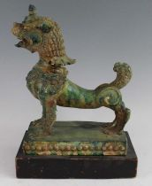 A Chinese green glazed pottery figure of a Fu Lion, modelled in proud standing pose, mounted on a