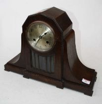 A 1920s oak cased eight-day mantel clock, the silvered dial showing Arabic numerals above a