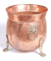 An early 20th century copper and brass jardiniere, flanked by brass lion mask ring handles, standing