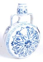 A Chinese export blue and white glazed stoneware moon vase, the neck flanked by twin strap