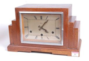 A 1930s Art Deco oak cased mantel clock, of stepped rectilinear form, the eight-day movement with