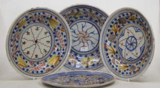 A set of three 20th century continental tin glazed dishes, 31cm dia. together with another similar