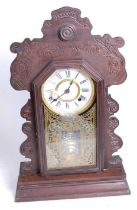 An early 20th century gingerbread type eight-day mantel clock, the chapter ring showing Roman
