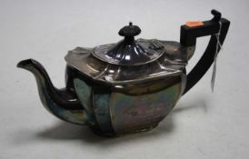 A George V silver teapot of shaped rectangular form having an ebonised finial and handle with