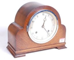 A 1930s oak cased eight-day mantel clock, the silvered chapter ring showing Arabic numerals, the