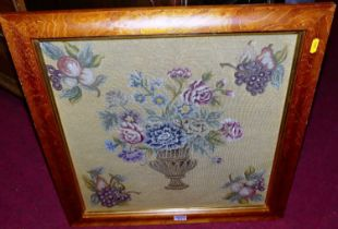 A framed woolwork panel depicting an urn issuing flowers, 43x43cm, in glazed frame, together with an
