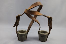 A pair of lead cups with leather straps as fastened to bulls' horns to prevent harm to other beasts