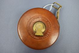 A vintage Rabone leather-covered Imperial tape measure, the brass crank bearing a struck British