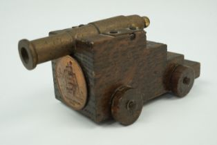"""A small model naval canon, its truck bearing a copper plaque with the legend """"HMS Victory, 1765"""" and"""