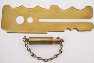 A brass button stick together with a rifle bore scope
