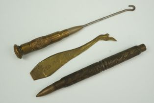A Great War trench art button hook, a rifle cartridge pencil and a novelty in the form of a lady's