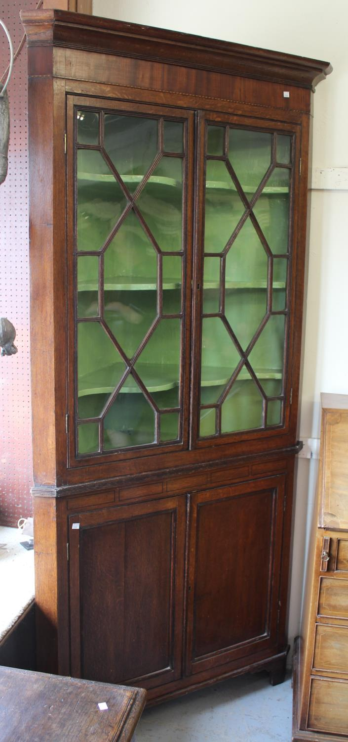 George III oak standing corner cabinet with a moulded cornice above a pair of astragal glazed doors,