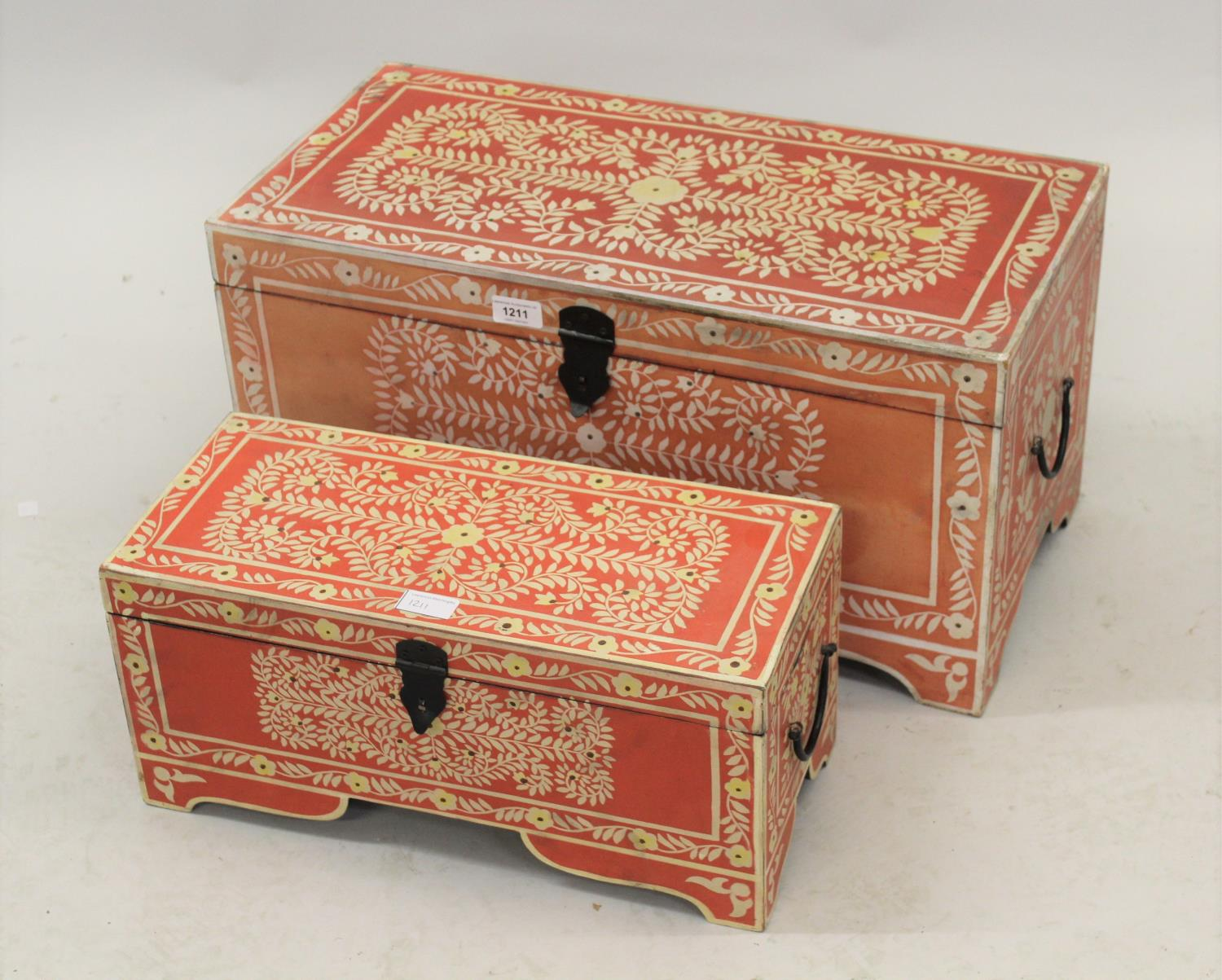 Two modern graduated storage boxes with hinged cover and floral decoration on a red ground, 12ins
