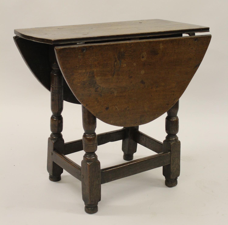 Charles II small oak drop leaf stool / table, circa 1680, the oval hinged top raised on turned