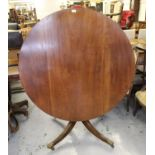 Circular mahogany tilt top pedestal dining table with a turned column support and quadruped base