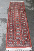 Pakistan runner of Turkoman design, 6ft x 2ft approximately together with a similar smaller rug