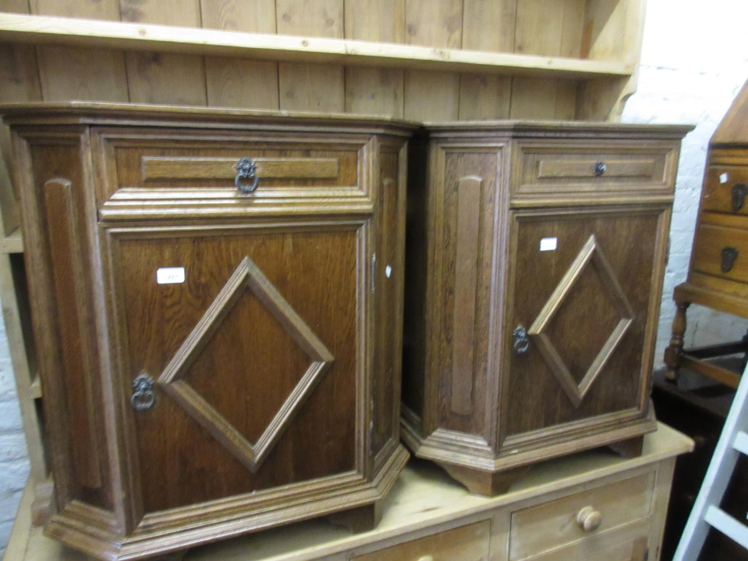 Pair of reproduction oak bedside cabinets with moulded panel doors and canted corners, together with