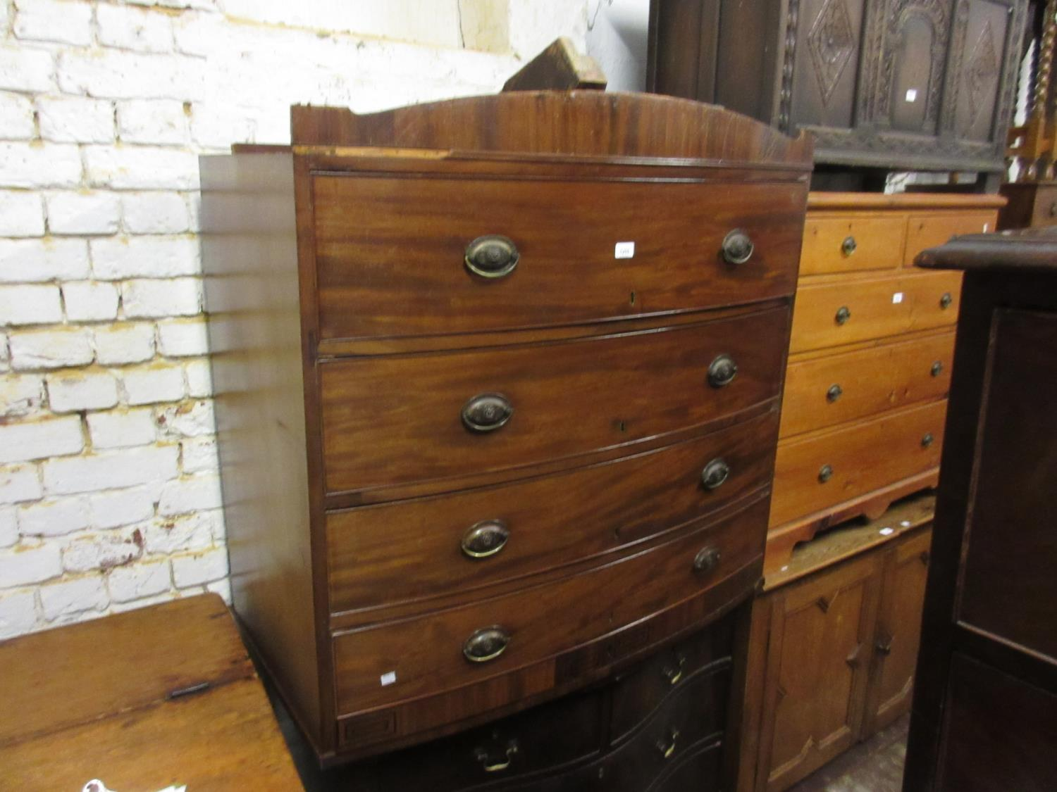 Regency mahogany black line inlaid bow fronted chest of four long drawers with oval brass handles,
