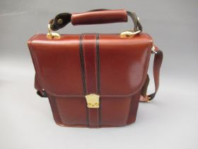 Brown leather bag with black trim, gold tone hardware, shoulder strap and carrying handle
